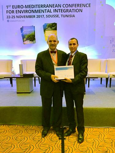 プレゼンターから賞を受取る第一著者のMokhtar Guizani 氏(右)