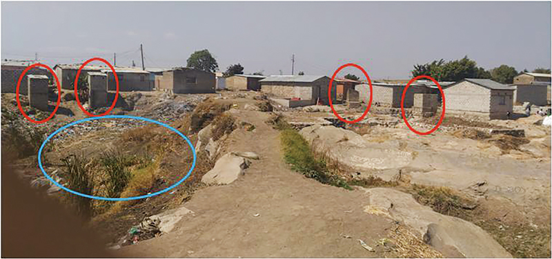 Photo Toilet (red mark in the Photo) and open defecation zone (blue mark) in Kanyama district in Lusaka City, Zambia (Photo by Sikopo P Nyambe)